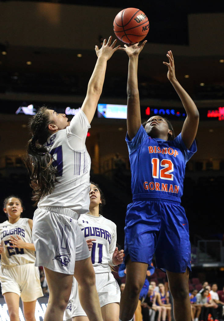 Bishop Gorman's Aaliyah Bey (12) reaches for the ball over Spanish Springs' Mariah Barraza (33) during the first half of a Class 4A state girls basketball semifinal game at the Orleans Arena in La ...