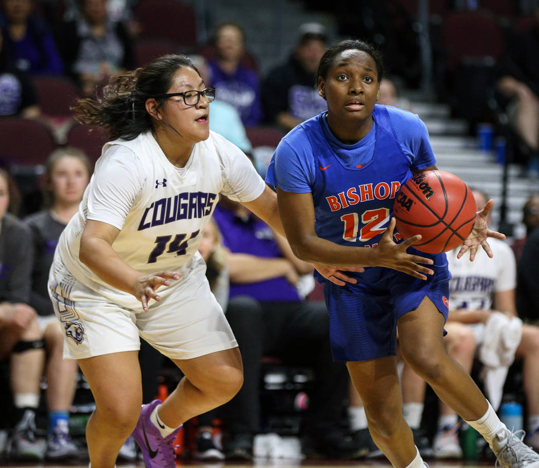 Bishop Gorman's Aaliyah Bey (12) looks to pass the ball while being guarded by Spanish Springs' Autumn Wadsworth (14) during the first half of a Class 4A state girls basketball semifinal game at t ...
