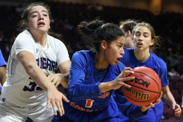 Bishop Gorman's Caira Young (1) protects the ball while being guarded by Spanish Springs' Mariah Barraza (33) during the second half of a Class 4A state girls basketball semifinal game at the Orle ...