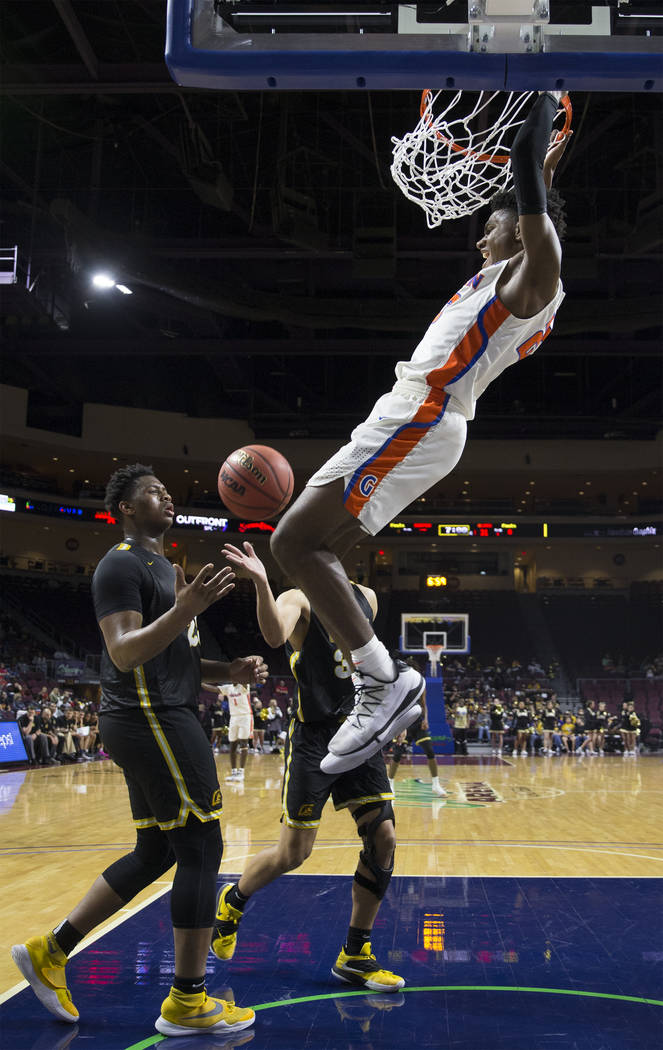 Bishop Gorman junior forward Mwani Wilkinson (23) dunks over Clark senior forward Antwon Jackson (23) in the third quarter of the Class 4A boys state championship game on Friday, March 1, 2019, at ...