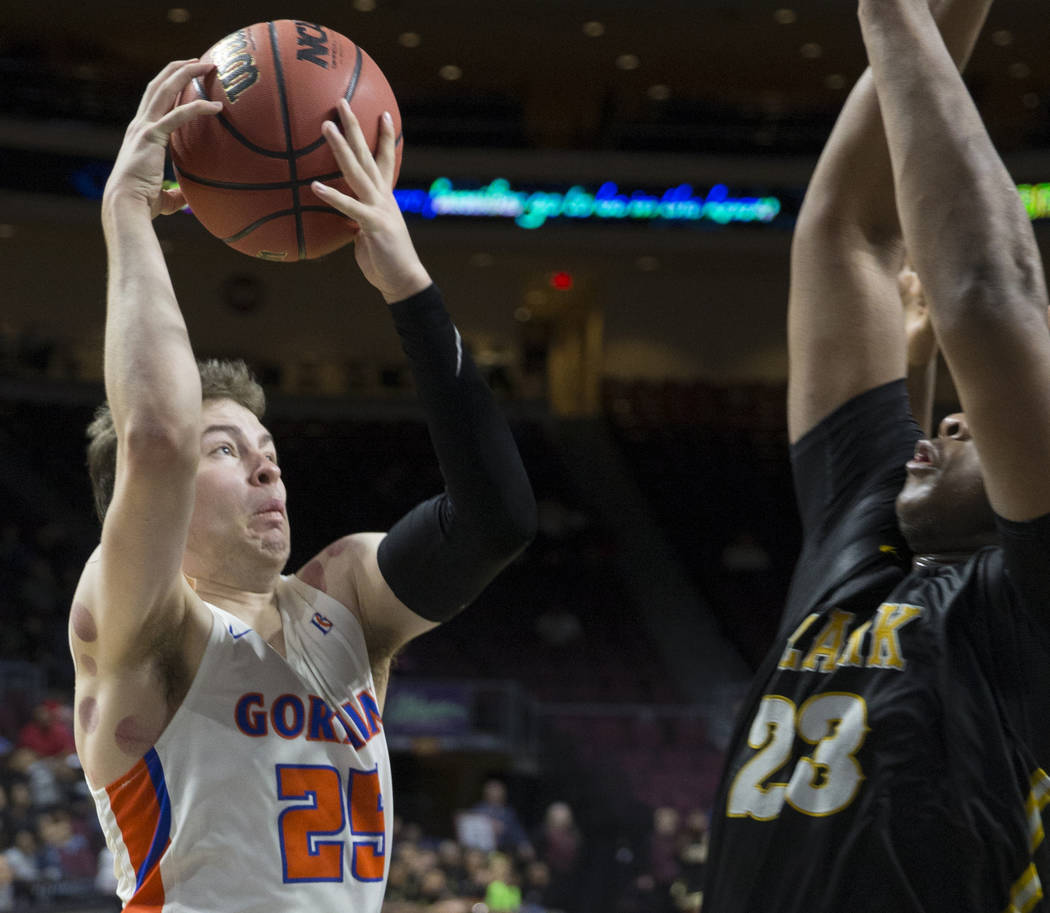 Bishop Gorman senior guard Chance Michels (25) drives over Clark senior forward Antwon Jackson (23) in the fourth quarter of the Class 4A boys state championship game on Friday, March 1, 2019, at ...