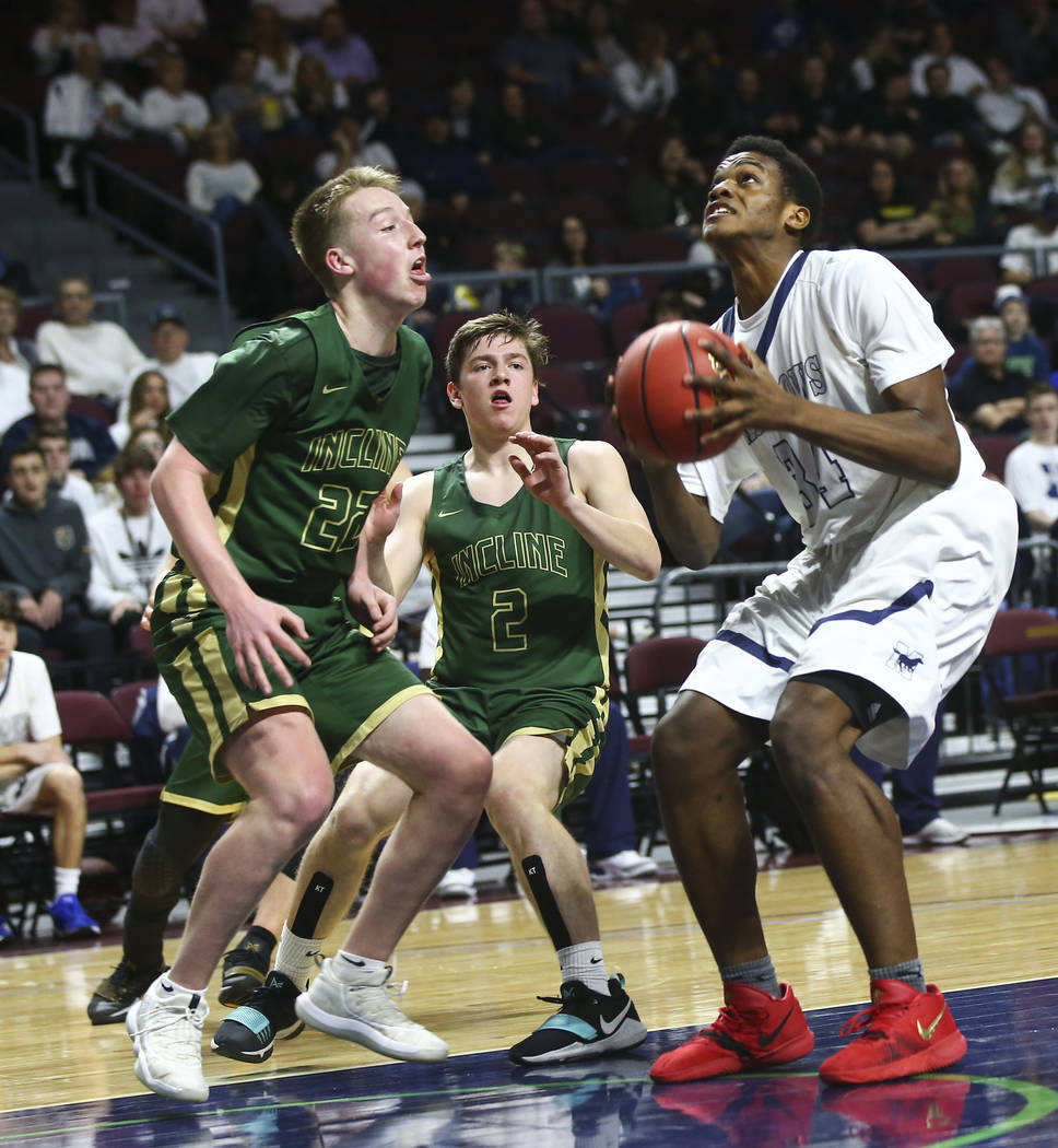 The Meadows Obinna Ezeanolue (34) looks to shoot against Incline guard Liam Nolan-Bowers (22) and Brad Rye (2) during the second half of the Class 2A boys basketball state championship game at the ...