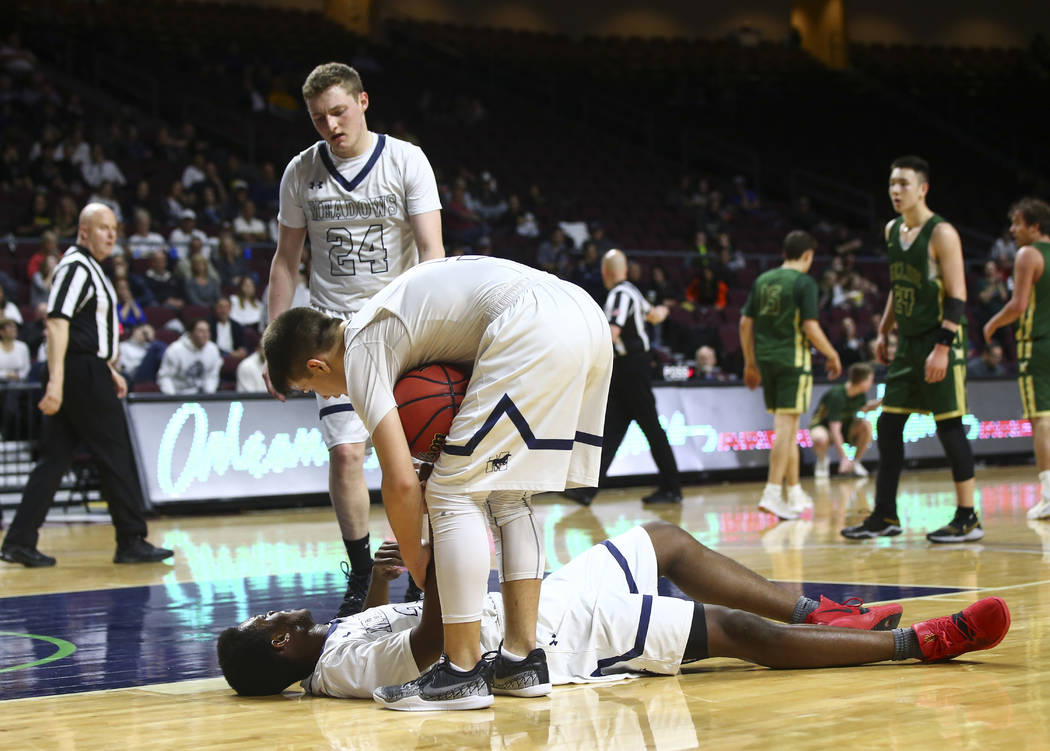 The Meadows guard Allen Fridman (24) and Trey Covell (5) check on teammate Obinna Ezeanolue during the second half of the Class 2A boys basketball state championship game against Incline at the O ...