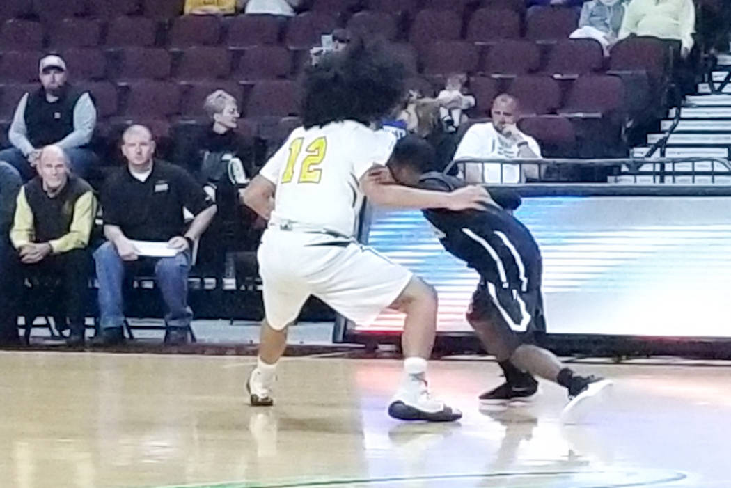 Spring Mountain's Tony Branch, right, looks for a driving lane as Mineral County's Robert McFalls defends in the Class 1A boys state championship game at Orleans Arena on Saturday, March 2, 2019. ...