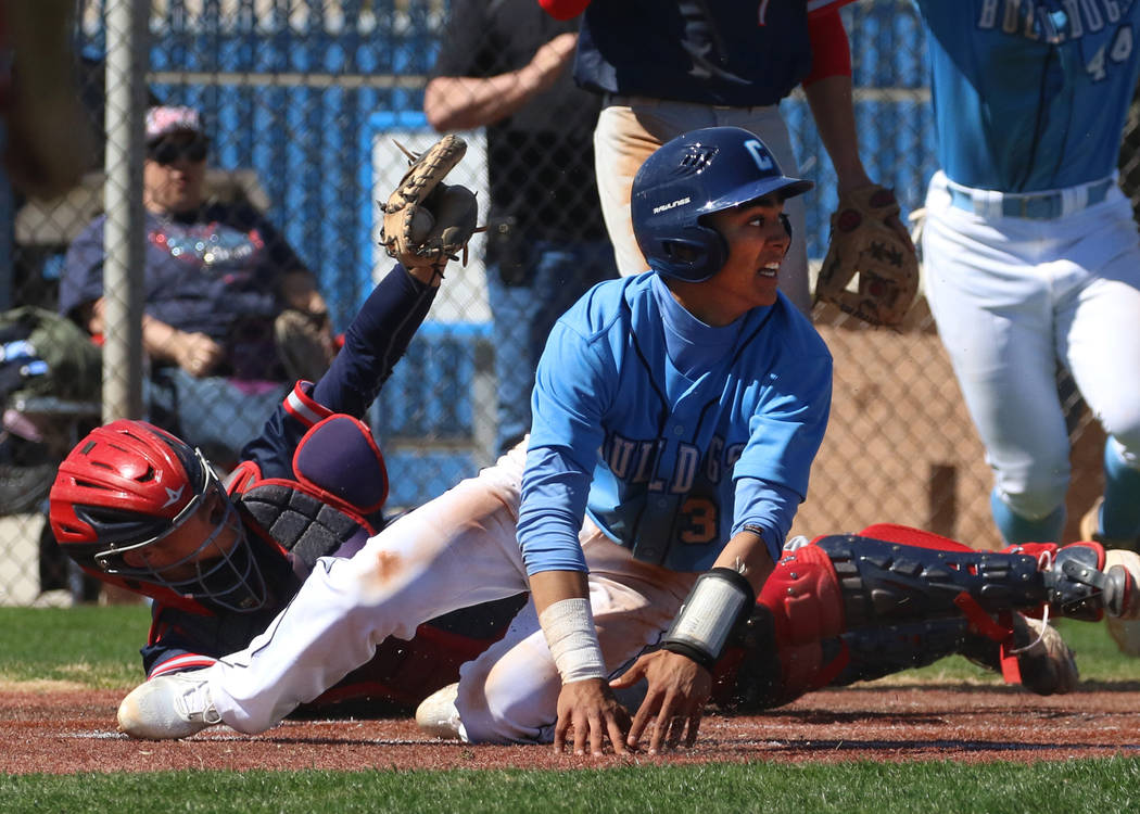Centennial's Anthony Martinez, center, avoids a tag from Liberty's catcher James Katona as he scores the winning run during their baseball game at Centennial High School on Thursday, March 7, 2019 ...