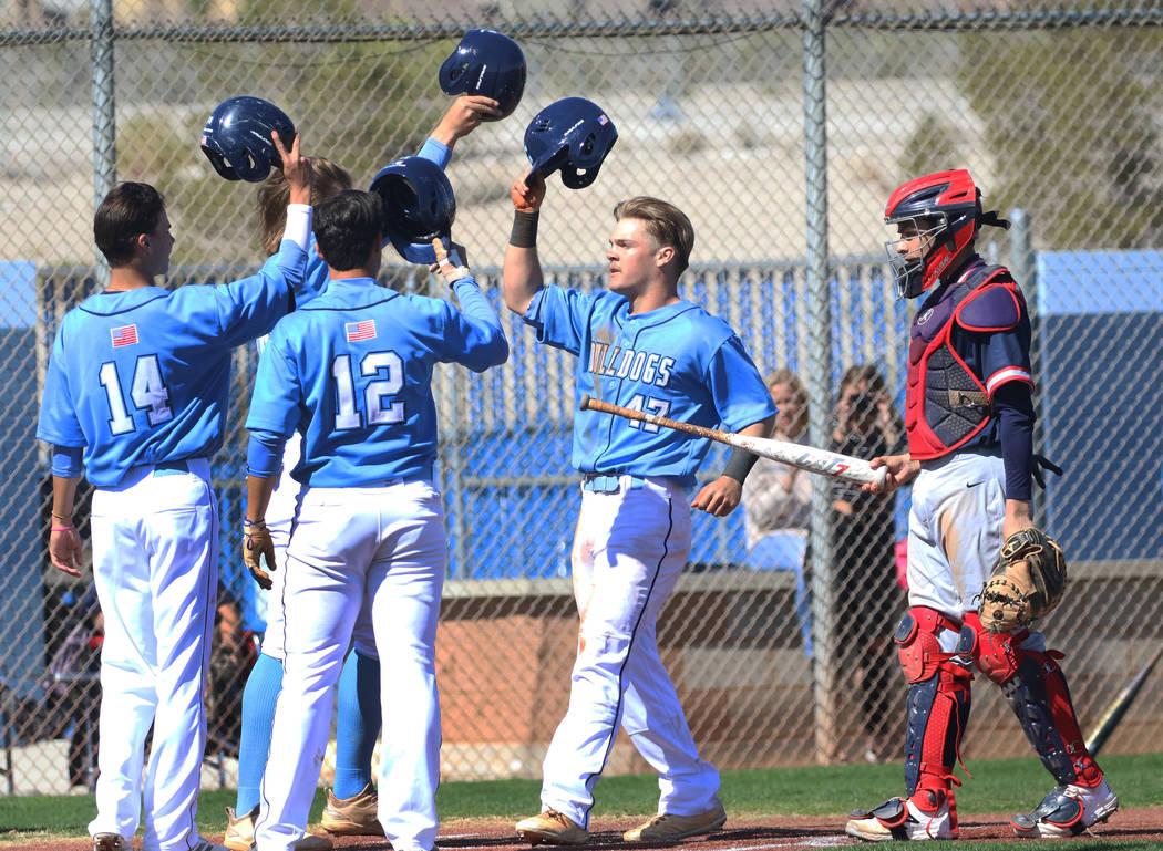 Centennial's Austin Kryszczuk (47) celebrates with his teammates after hitting a 3-run homer as Liberty's catcher James Katona looks on during their baseball game at Centennial High School on Thur ...