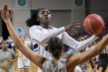 Centennial senior Eboni Walker (22) drives past Bishop Gorman senior Olivia Smith (11) in the first quarter of the Class 4A girls state championship game on Friday, March 1, 2019, at Orleans Arena ...