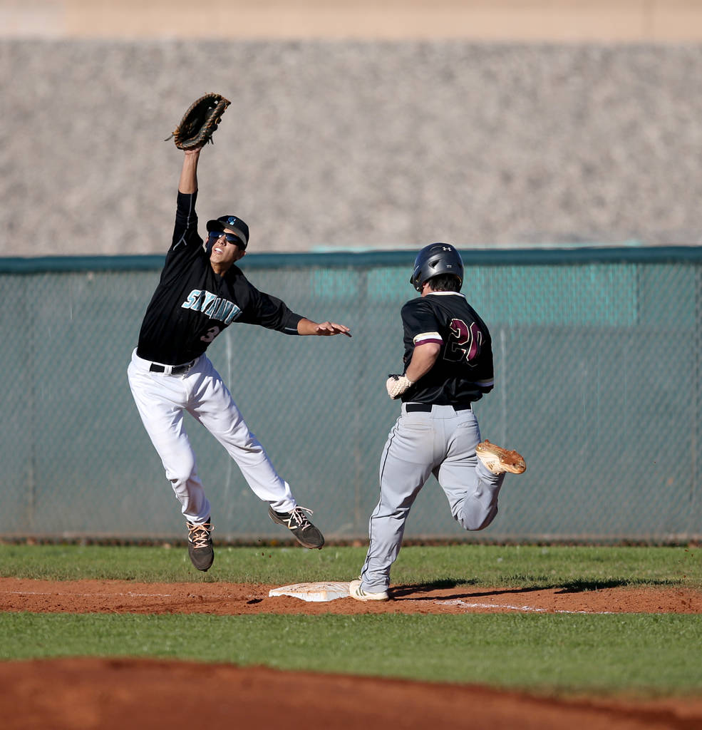 Faith Lutheran Dylan Howell (20) crosses first base as Silverado first baseman Jarod Hill (30) pulls in a high throw during a baseball game at Silverado High School in Las Vegas Friday, March 8, 2 ...