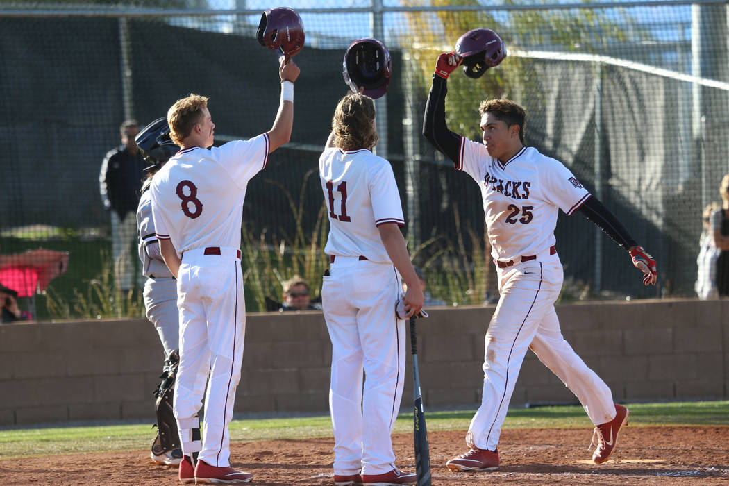 Desert Oasis' Aaron Roberts (25) scores a run with a home run and celebrates with teammates Josh Sharman (11) and Zac Czerniawski (8) in the baseball game against Palo Verde at Desert Oasis High S ...