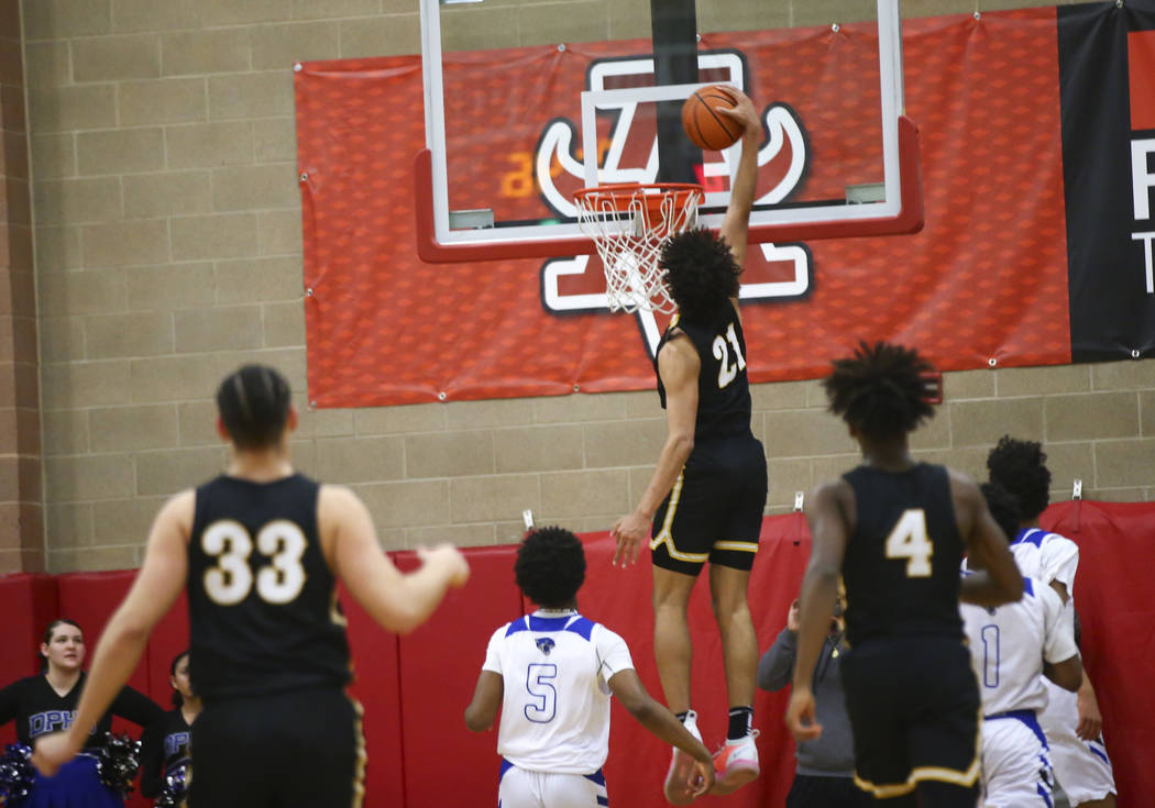 Clark's Jalen Hill (21) dunks in front of Desert Pines' Malik Brooks (5) during the first half of a Class 4A state boys basketball quarterfinal game at Arbor View High School in Las Vegas on Wedne ...