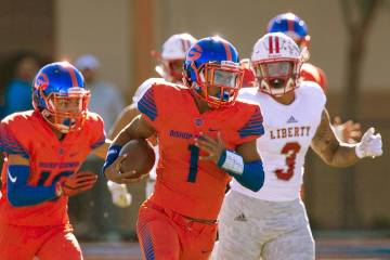 Bishop Gorman's Micah Bowens (1) carries the ball past Liberty's Zephania Maea during the first half of the Desert Region championship game at Bishop Gorman High School on Saturday, Nov. 24, 2018. ...