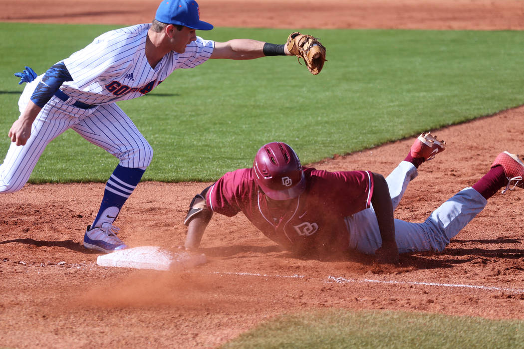Desert Oasis' Jacob Walsh (21) slides back to first base safely against Bishop Gorman's John Gaughan (5) in the baseball game at Bishop Gorman High School in Las Vegas, Thursday, March 21, 2019. E ...