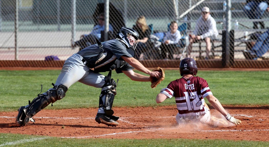 Cimarron-Memorial baserunner Anthony Ortiz (12) slides safely across home plate under the tag of Silverado catcher Brant Hunt (18) in the third inning of their baseball game at Cimarron-Memorial H ...