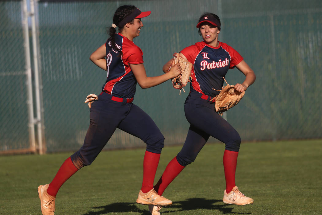 Liberty's Shelby Carvalho (13), left, and Maddison Hamilton (12), run to the dugout after a cat ...