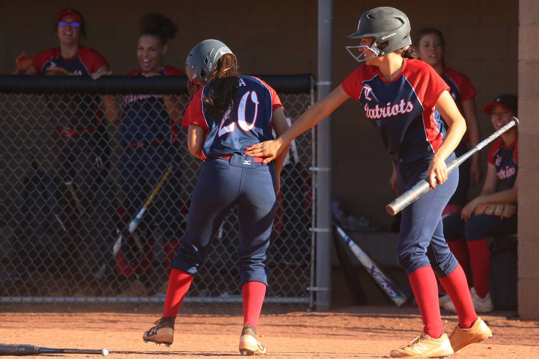 Liberty's Jessica Meza (20), left, celebrates her run with Shelby Carvalho (13) in the softball ...