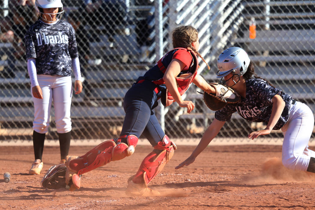 Liberty's McKenzie Hamilton (00) tags out Desert Oasis' Makayla Rickard (23) at home plate in t ...