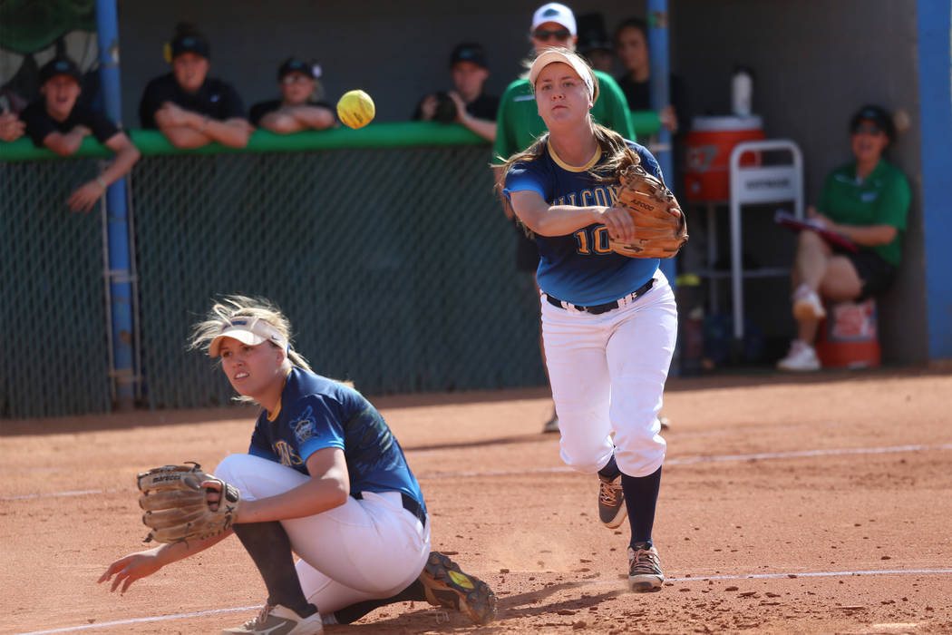 Foothill's Makenzie Andrews (10) throws to first base for an out as Leah Becker (5) ducks out o ...