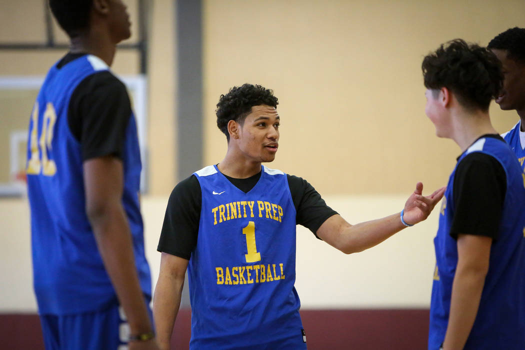 Trinity International junior Daishen Nix talks with his teammates during a practice at the Bill ...