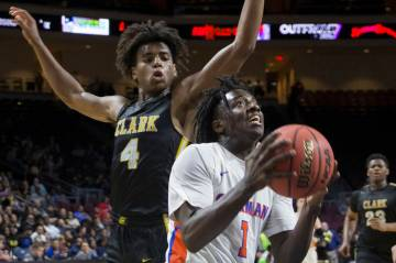 Bishop Gorman sophomore guard Will McClendon (1) drives past Clark senior guard Carlos Allen (4 ...