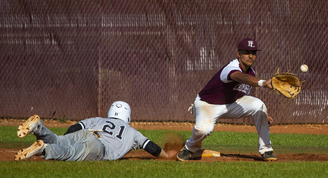 Palo Verde's Josiah Cromwick (21) dives back to first base ahead of a throw to Faith Lutheran's ...