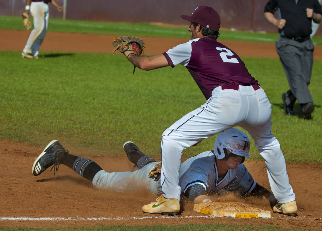 Palo Verde's Paul Myro IV (23) dives to tag third base ahead of a throw to Faith Lutheran's Mic ...