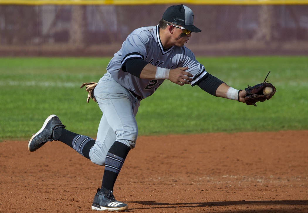 Palo Verde's Paul Myro (23) scoops up a grounder from a Faith Lutheran batter during their high ...