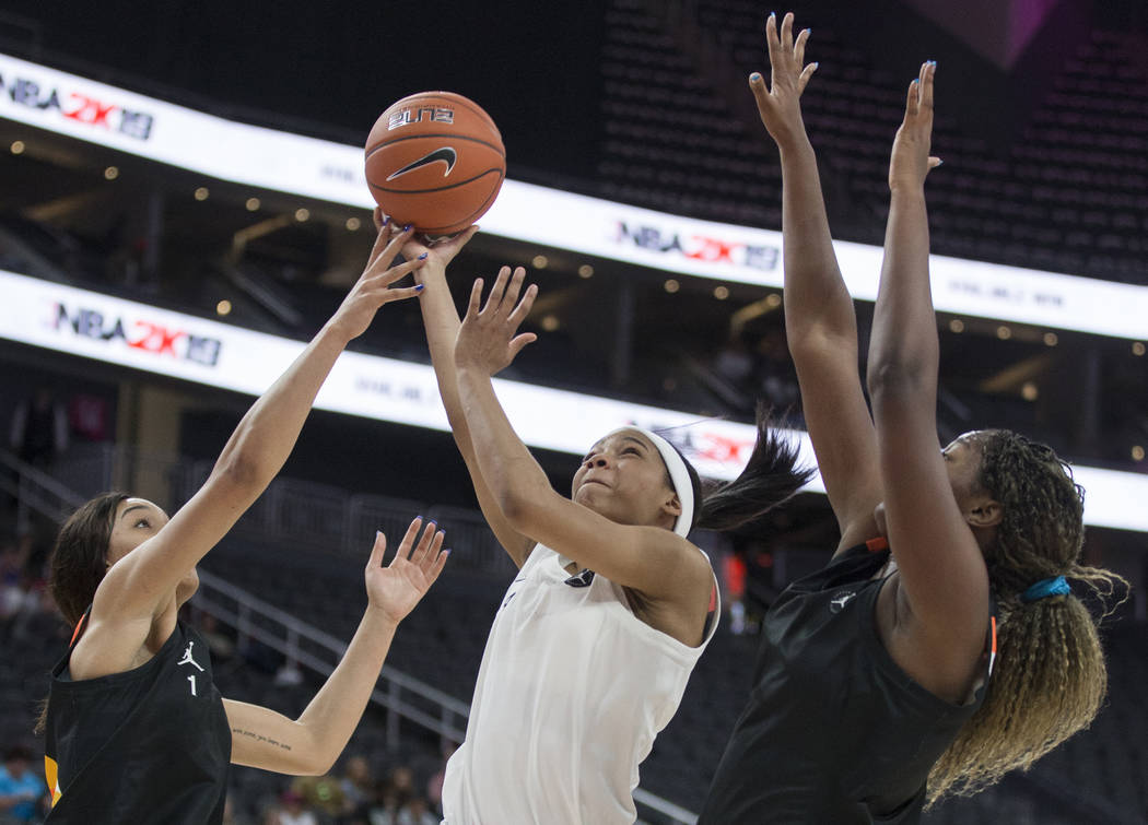 Zia Cooke (4) slices to the rim past Breanna Beal (1) and Lavender Briggs (23) in the second qu ...