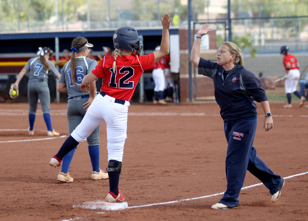Coronado baserunner Paige Sinicki (12) high-fives head coach Melissa Krueger after hitting a tr ...