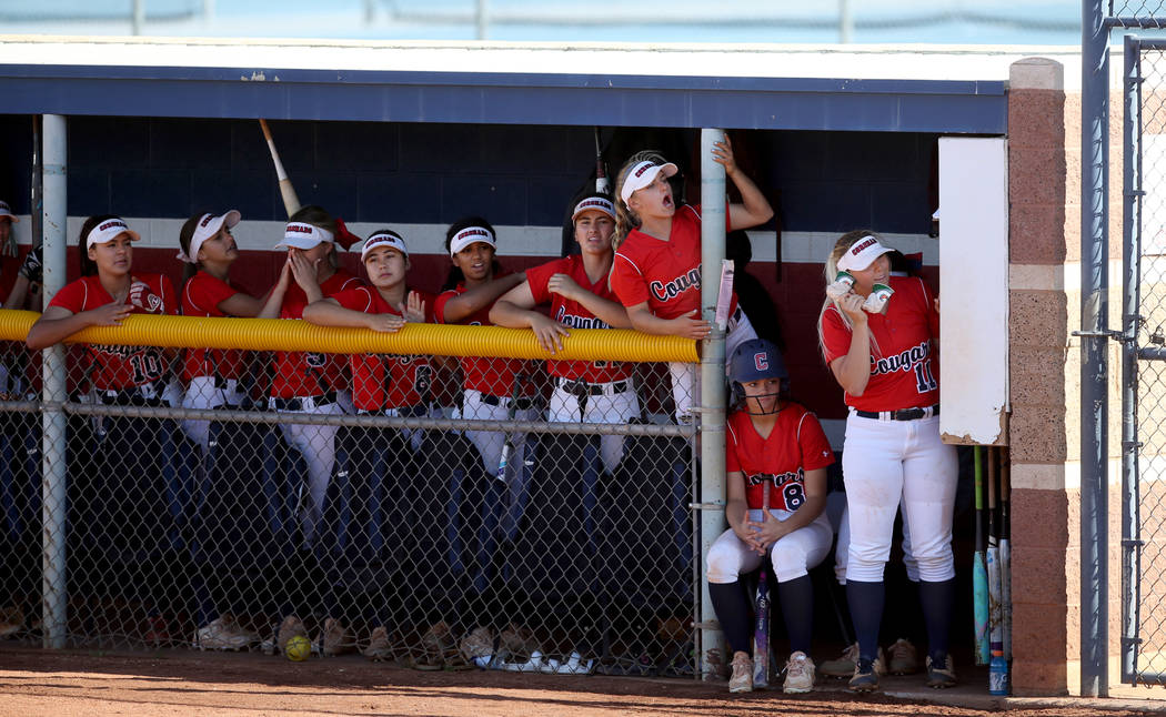 Coronado's Paige Sinicki (12), standing on chair, cheers with her teammates in the first inning ...