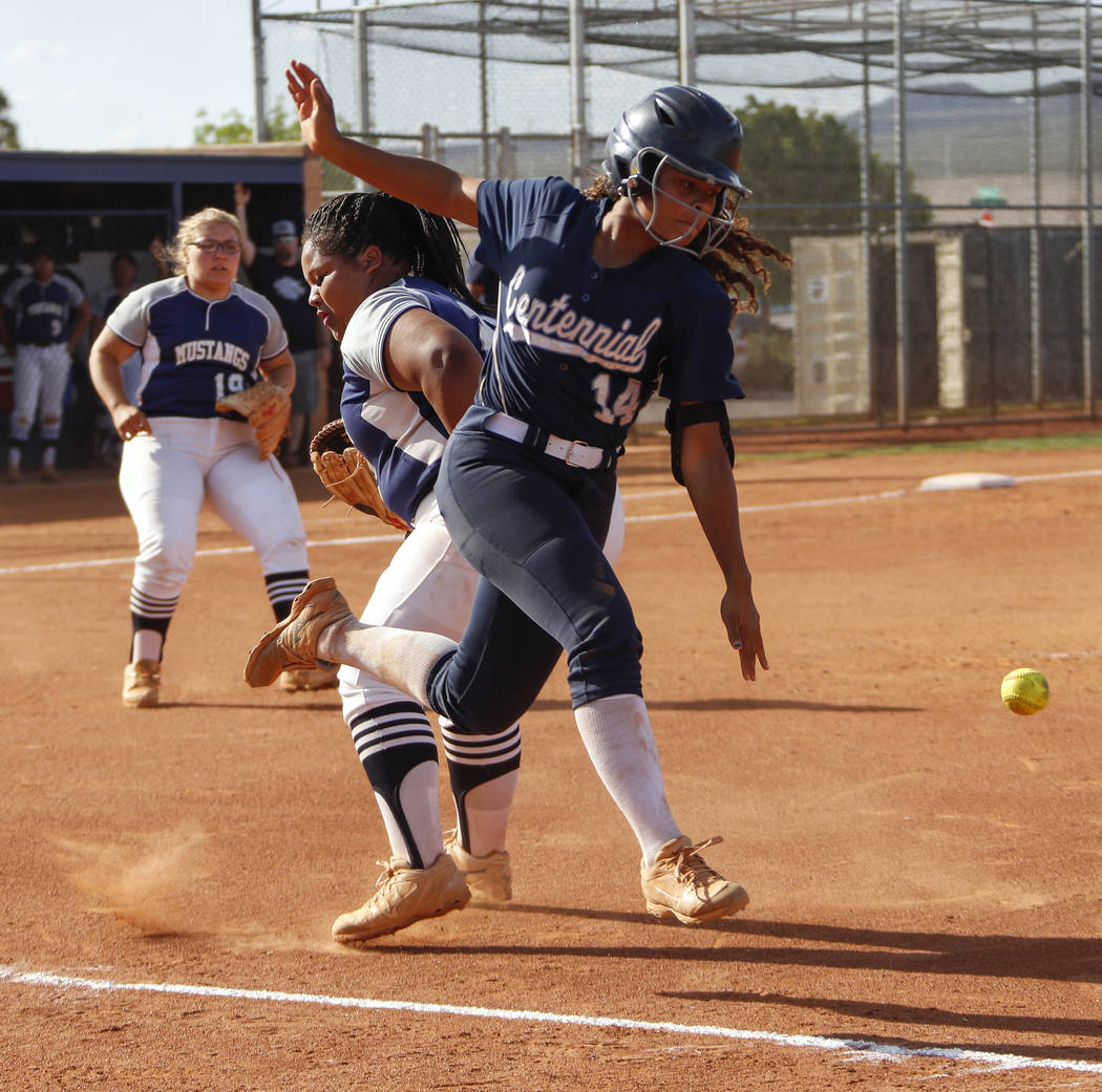Centennial outfielder Maddie Kallfelz (14) runs by Shadow Ridge first baseman Alyssa Stanley (2 ...