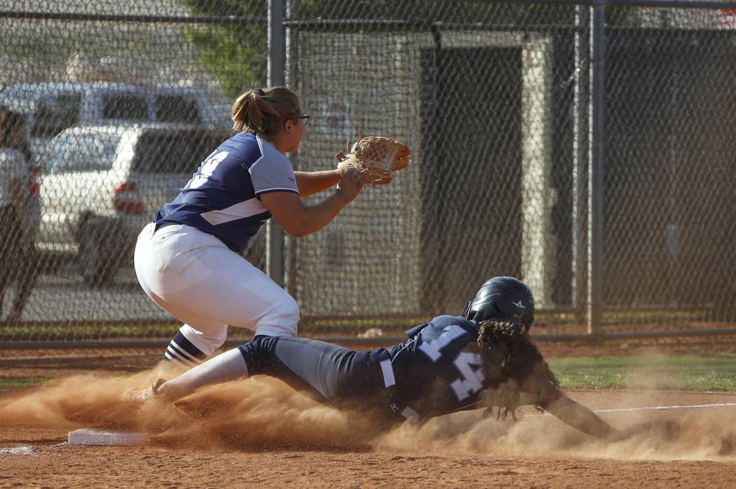 Centennial outfielder Maddie Kallfelz (14) slides safely into third base as Shadow Ridge third ...