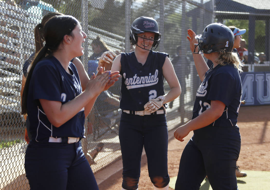 Centennial infielder Ryan Rogers (2) is cheered on by her teammates after scoring a run in the ...