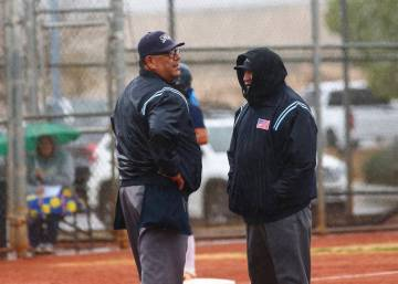 Umpires talk as rain comes down in the first inning of a softball game. (Chase Stevens/Las Vega ...