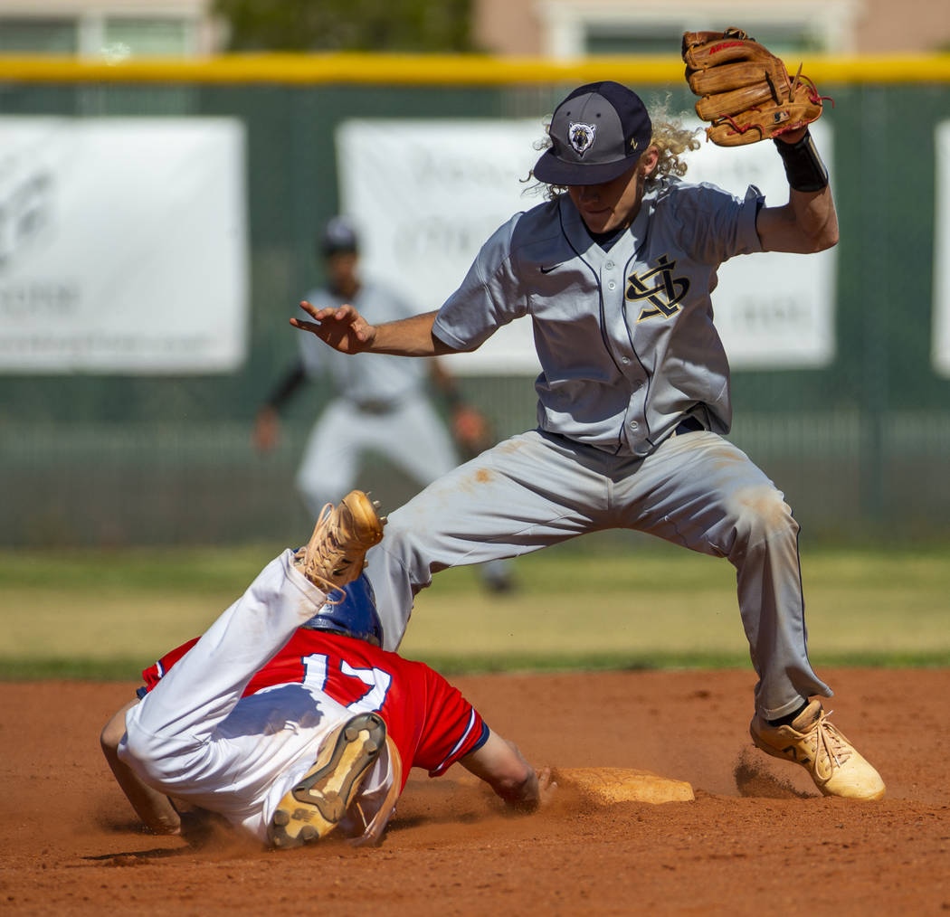 Liberty's Ethan Safier (17) dives back to second base below Spring Valley's Chasyn Love (23) du ...