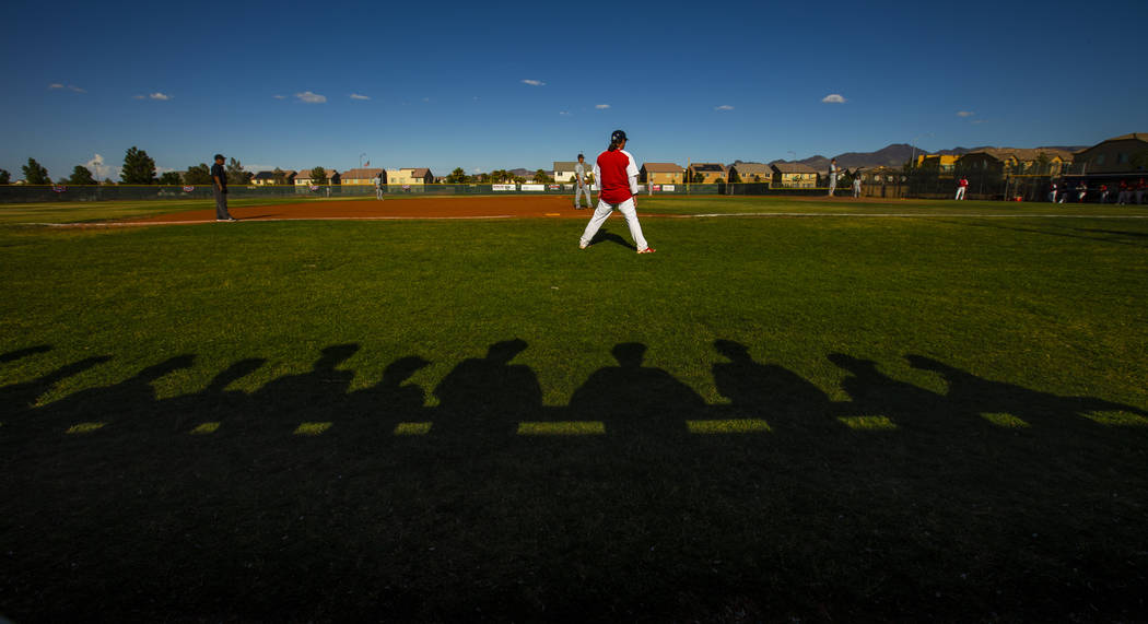 Spring Valley players are silhouetted behind Liberty head coach Rich Ebarb during the first rou ...