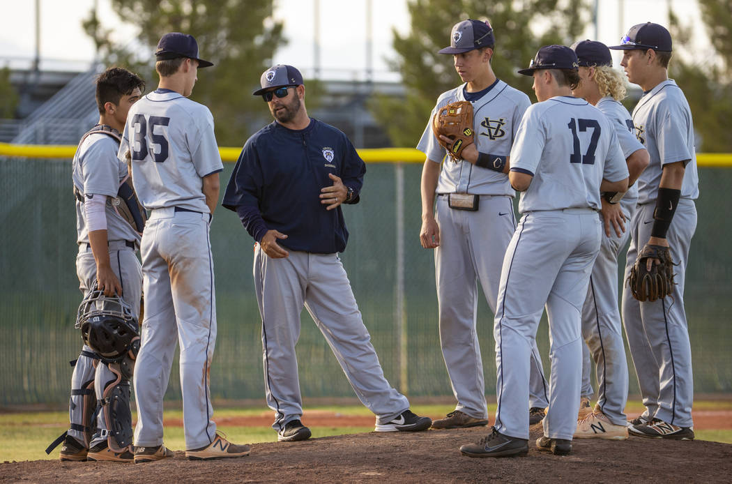 Spring Valley head coach Paul Bassett meets with his players during a time out versus Liberty i ...