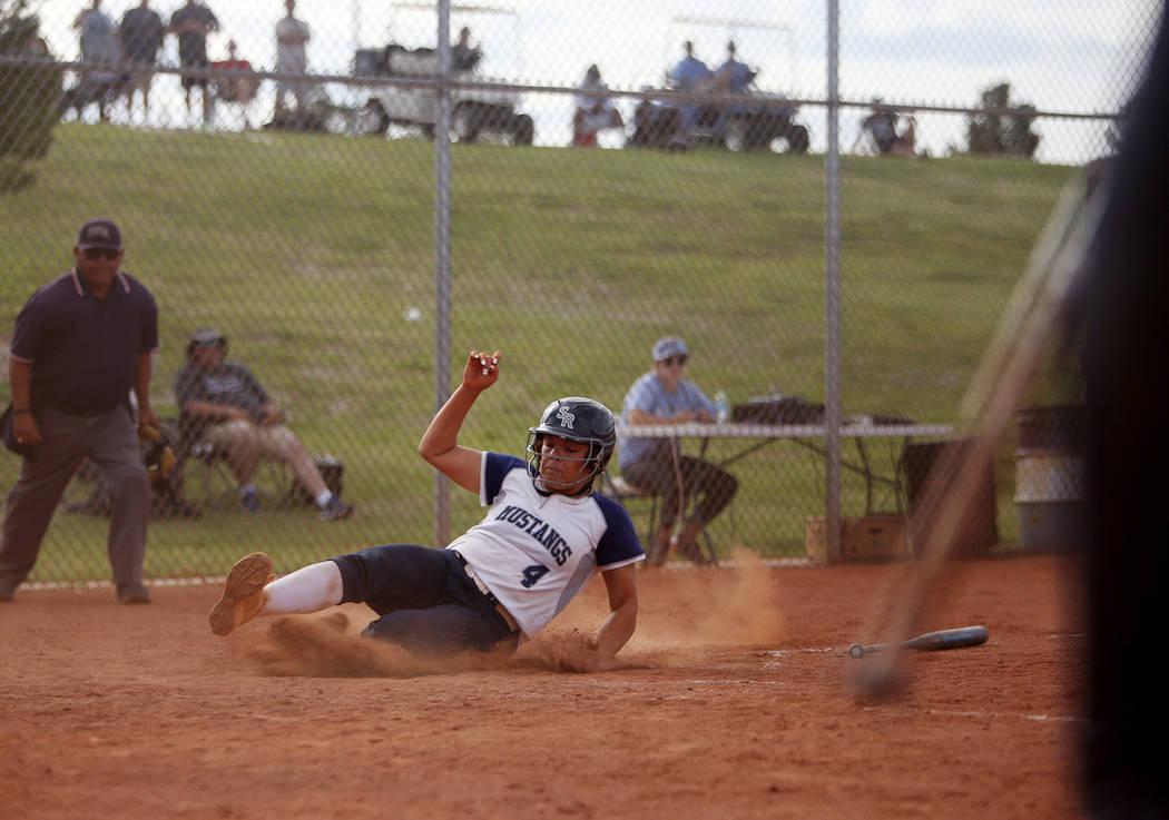 Shadow Ridge High School's Shea Clements (4) slides to make home base against Centennial High S ...