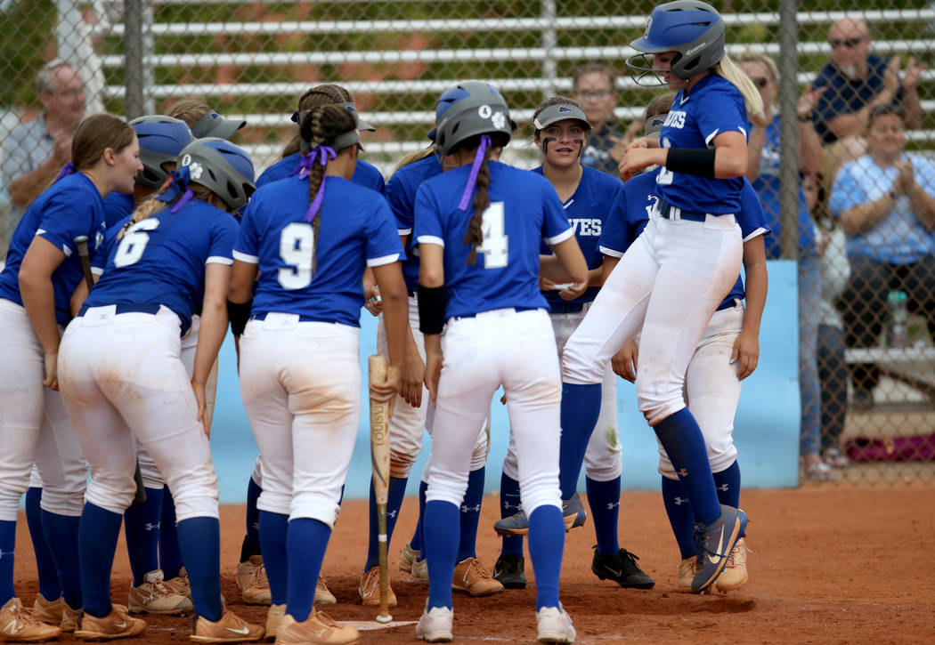 Basic's Sierra McClean (12) hops onto home plate with her teammates in the fourth inning of the ...