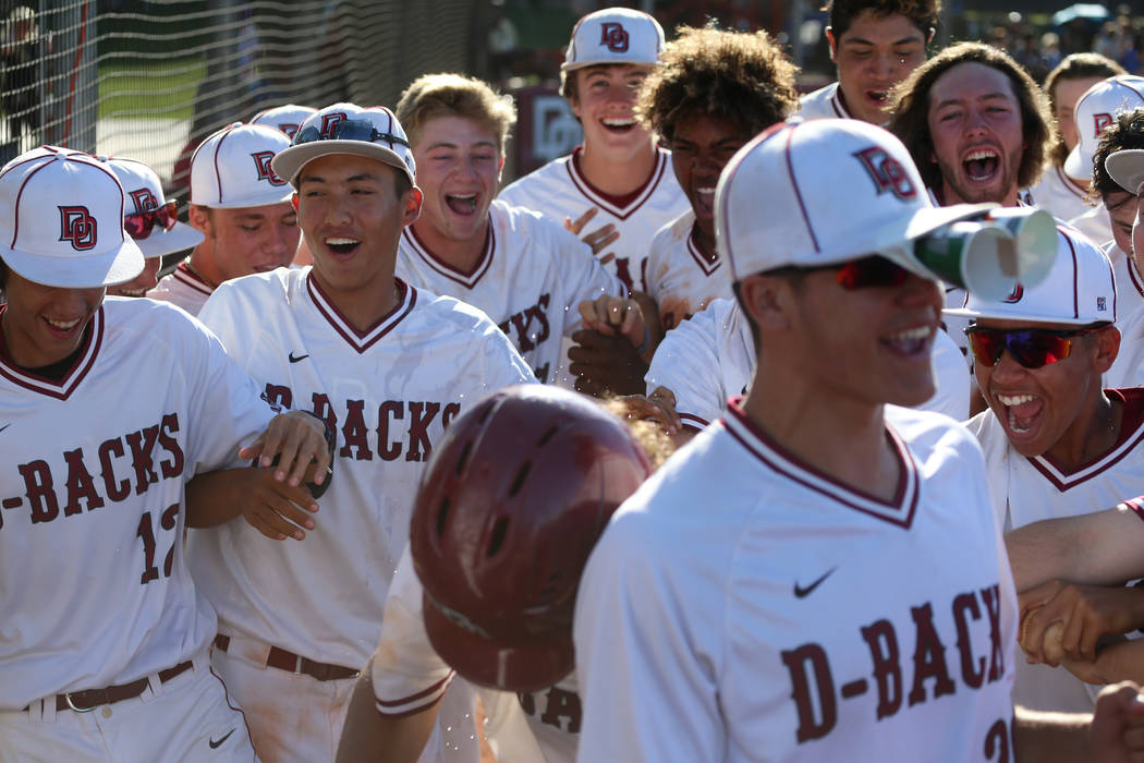 Desert Oasis celebrate a two run homer by Campbell Holt (16) against Basic in the Desert Region ...