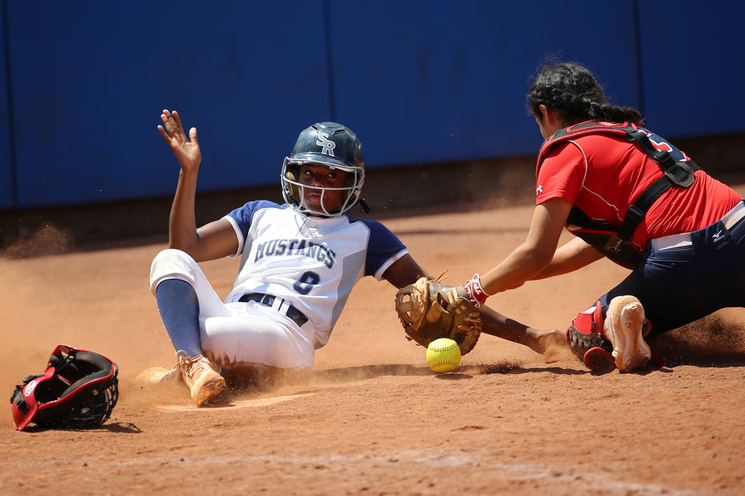 Shadow Ridge's Jasmine Martin (8) slides safe to home base for a run against Coronado's Isabel ...