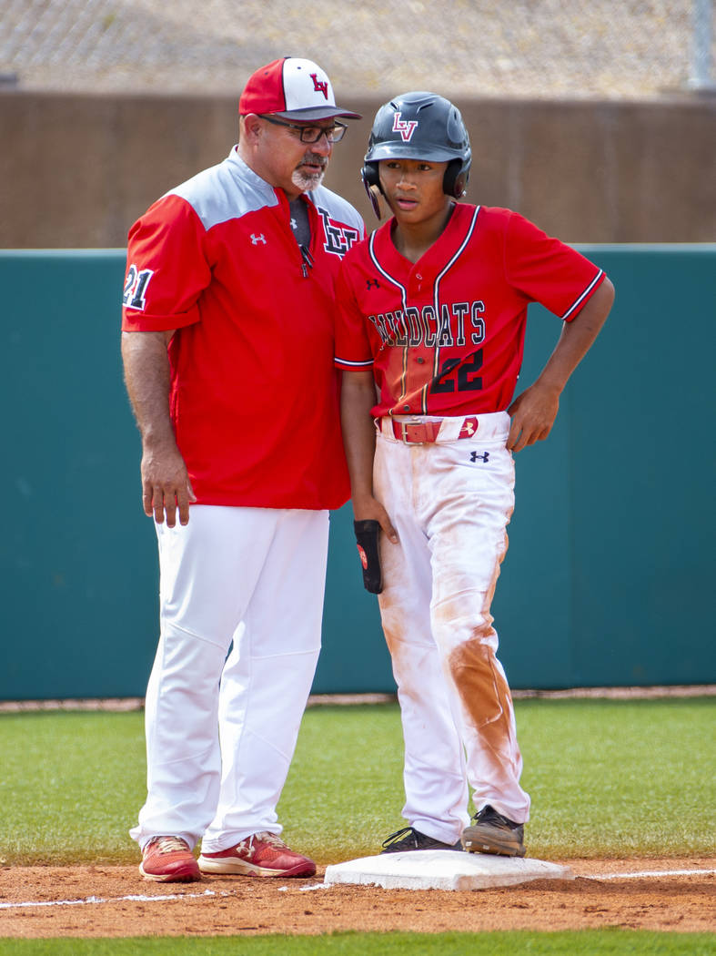 Longtime Las Vegas High coach Sam Thomas instructs runner Layne Adaro (22) at third base during ...