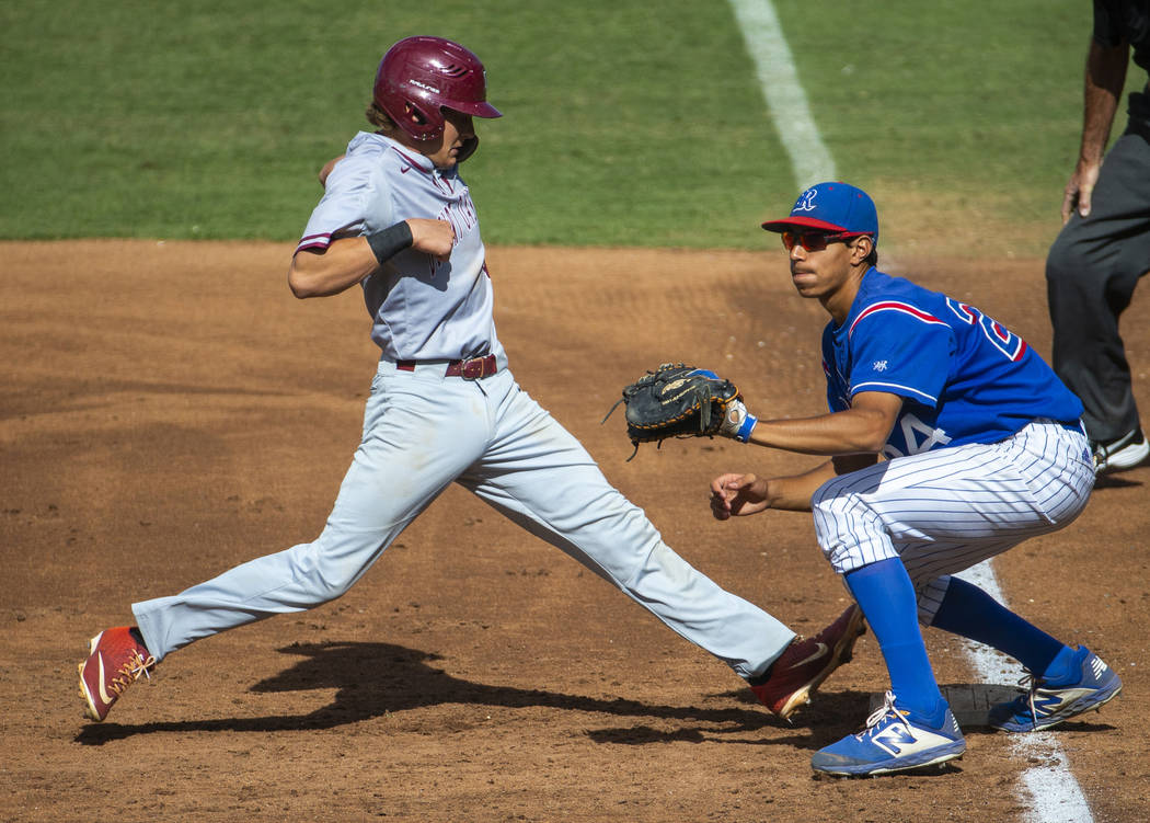 Desert Oasis runner Parker Schmidt (4) extends safely back to first base past Reno's Skylar Hal ...