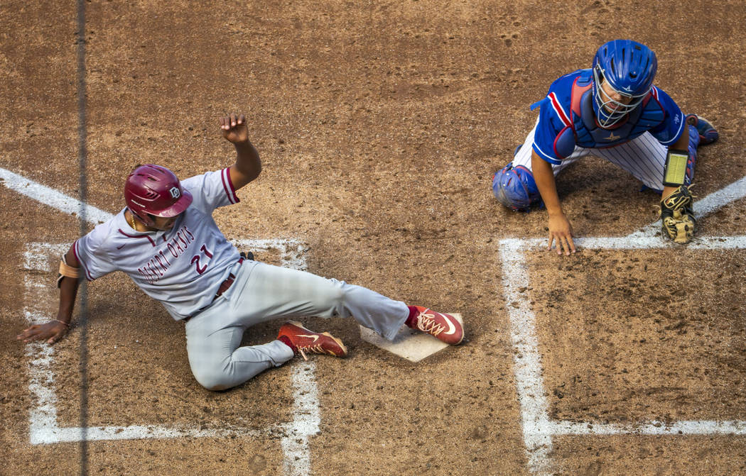 Desert Oasis runner Jacob Walsh (21) slides home safely past Reno catcher Lane Oliphant (28) in ...