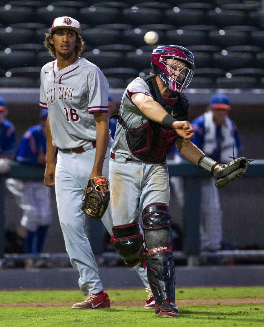 Desert Oasis pitcher DJ Jefferson Jr. (16) looks on as catcher Parker Schmidt (4) makes a throw ...