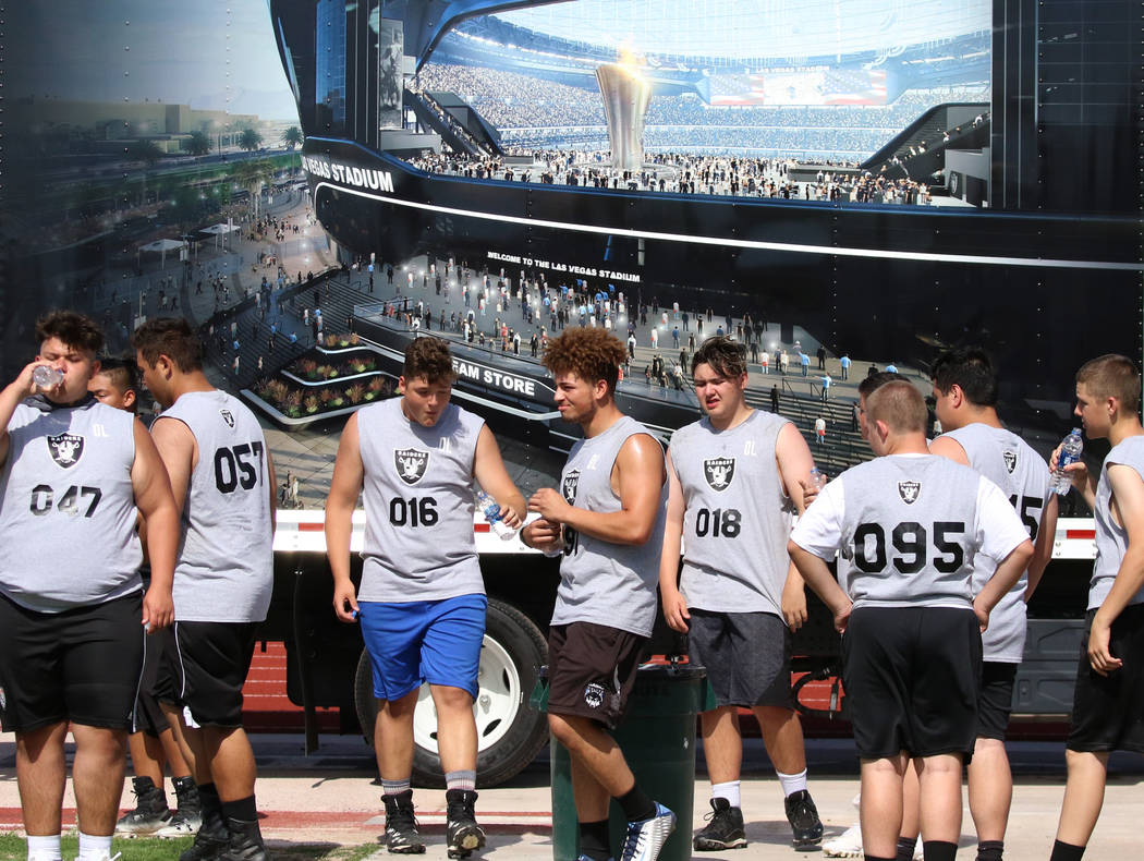 Local Clark County-area high school football players take a break as they participate in fundam ...