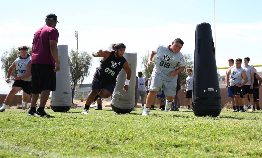 Leland Sparks, left, lead manager for Raiders football camp, watches as local Clark County area ...