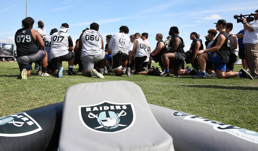 Local Clark County area high school football players listen to Reggie Kinlaw, second left, a f ...