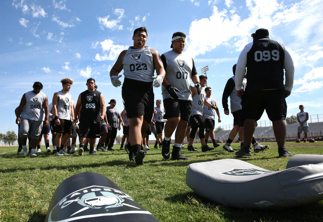 Former Faith Lutheran high school's offensive line coach De'Andre Nicholas, right, watches as L ...
