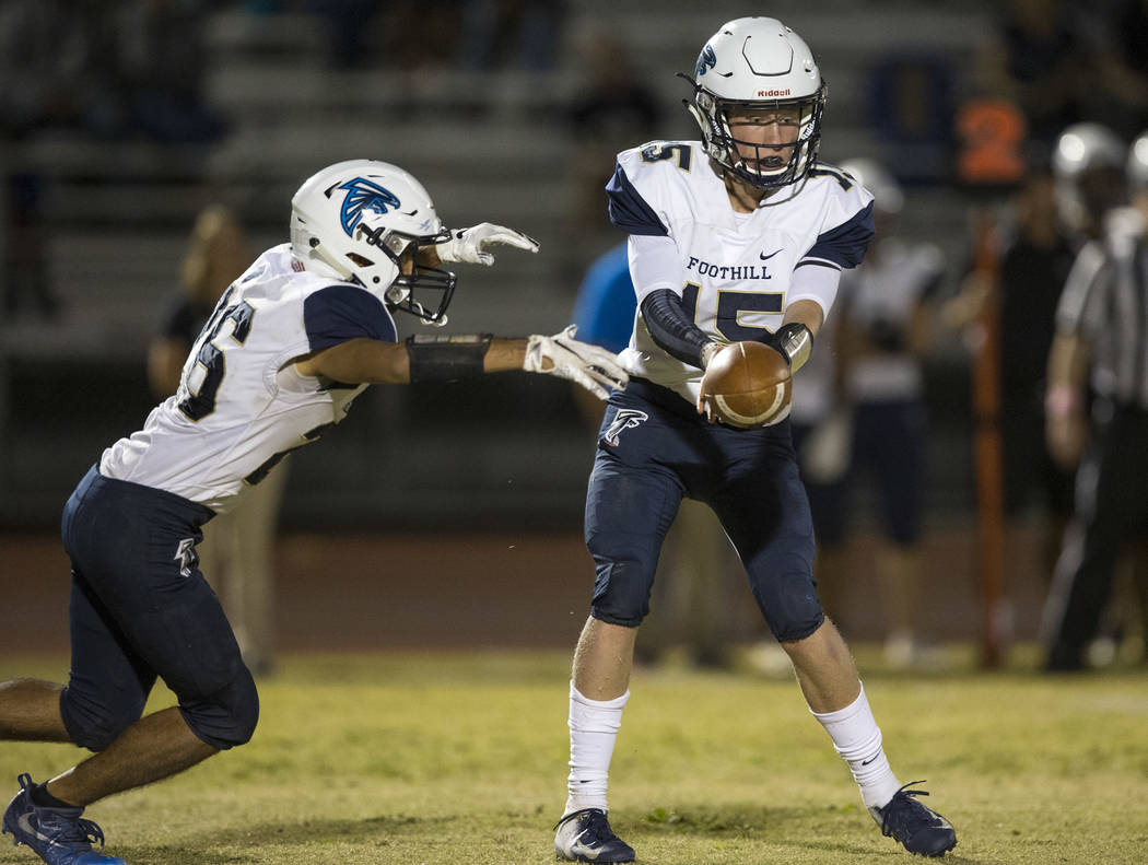 Foothill quarterback Koy Riggin (15) hands off the ball to running back Mario Armendariz (26) a ...